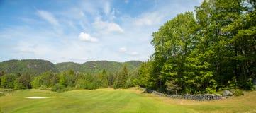 Ajardine em um campo de golfe com grama verde, árvores, céu azul bonito, panorama Fotografia de Stock Royalty Free
