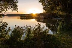 Ajardine em um lago com árvores e juncos e boatshouse Foto de Stock Royalty Free
