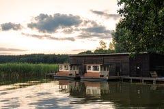 Ajardine em um lago com árvores e juncos e boatshouse Fotos de Stock