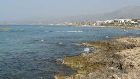 Ajardine en la playa de Stalis en la bahía de Malia en Creta Grecia Gente que goza de la playa Rocas en agua barras y restaurante metrajes