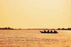Ajardine en la puesta del sol de un barco con los pescadores que pescan en Pantanal fotos de archivo