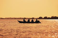 Ajardine en la puesta del sol de un barco con los pescadores que pescan en Pantanal imágenes de archivo libres de regalías