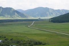Ajardine a estrada às montanhas um taiga e um rio Imagens de Stock
