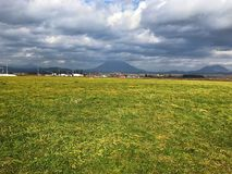 Ajardine a foto da grama, do céu azul, da nuvem e da montanha Imagens de Stock