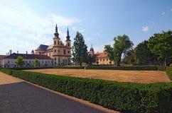 Ajardine a foto da igreja de Piarist da descoberta Vista do parque no castelo Litomysl no dia de verão fotos de stock royalty free