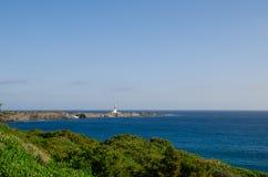 Ajardine a fotografia de um farol de Menorca no dia com rochas e mar Paisagem bonita Imagens de Stock
