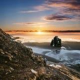 Ajardine Hvitserkur en Islandia, el caminar que viaja de los jóvenes abajo del acantilado a la playa negra de la arena en puesta  Fotografía de archivo libre de regalías
