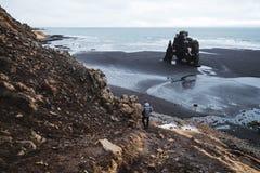 Ajardine Hvitserkur en Islandia, el caminar que viaja de los jóvenes abajo del acantilado a la playa negra de la arena por la mañ Imagenes de archivo