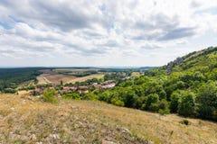 Ajardine a ideia da vila, do prado e da agricultura pequenos Floresta no lado direito com árvores verdes, céu azul, nuvens Imagens de Stock Royalty Free