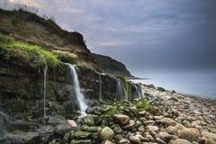 Ajardine a imagem da cachoeira larga que flui na praia rochosa na SU Foto de Stock
