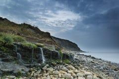 Ajardine a imagem da cachoeira larga que flui na praia rochosa na SU Fotos de Stock
