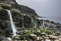 Ajardine a imagem da cachoeira larga que flui na praia rochosa na SU Fotografia de Stock Royalty Free
