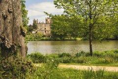 Ajardine a imagem da casa vitoriano velha vista através do lago na soma Fotos de Stock