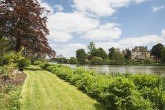 Ajardine a imagem da casa vitoriano velha vista através do lago na soma Imagem de Stock Royalty Free