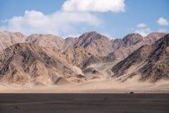 Ajardine a imagem das montanhas e do fundo do céu azul com povos e carros em Leh Ladakh Imagens de Stock