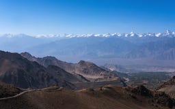 Ajardine a imagem das montanhas e dos carros na estrada em Ladakh com fundo do céu azul Fotografia de Stock Royalty Free