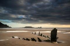 Ajardine a imagem do naufrágio velho na praia no por do sol no verão Fotos de Stock