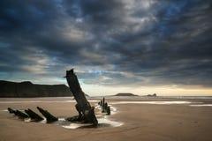Ajardine a imagem do naufrágio velho na praia no por do sol no verão Imagem de Stock