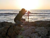Ajardine la fotografía tirada con el fotógrafo que pone su cámara en una playa en la puesta del sol foto de archivo