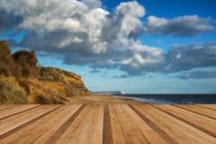 Ajardine la puesta del sol del vivd sobre la playa y los acantilados con los tablones de madera f Imagen de archivo libre de regalías