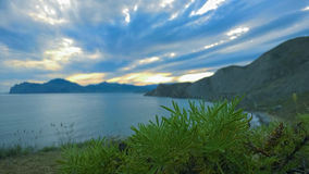 Ajardine la puesta del sol en un fondo de montañas y del mar Fotos de archivo