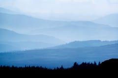 Ajardine la visión desde el top de la montaña en mañana brumosa a través del coun Imagen de archivo libre de regalías