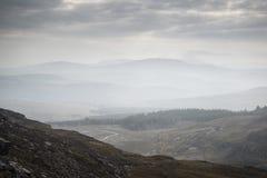 Ajardine la visión desde el top de la montaña en mañana brumosa a través del coun Imágenes de archivo libres de regalías