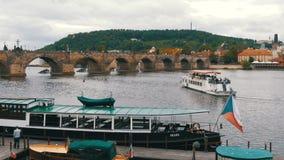 Ajardine la vista del puente y del barco de Praga que flotan en el río Moldava almacen de metraje de vídeo