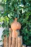Ajardine las jarras de las jarras de la arcilla del diseño en una cerca de madera tejida Imagen de archivo libre de regalías