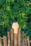 Ajardine las jarras de las jarras de la arcilla del diseño en una cerca de madera tejida Foto de archivo libre de regalías