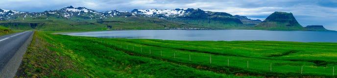 Ajardine, a montanha de Kirkjufell, e a cidade Grundarfjordur Imagem de Stock