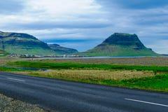 Ajardine, a montanha de Kirkjufell, e a cidade Grundarfjordur Foto de Stock Royalty Free