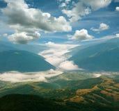 Ajardine montes da montanha na névoa sob o céu azul Imagens de Stock