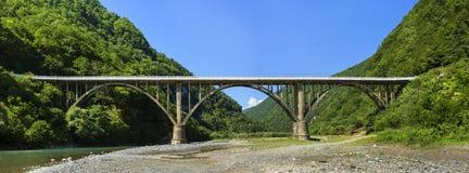 Ajardine na Abkhásia com a ponte de pedra sobre o rio fotos de stock