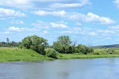 Ajardine nas costas do rio e do campo com grama verde Fotografia de Stock Royalty Free
