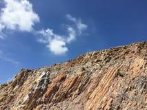 Ajardine nas montanhas e na obscuridade - céu azul com nuvens Fotografia de Stock Royalty Free