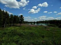 Ajardine no lago com costas verdes e o céu azul Fotografia de Stock Royalty Free