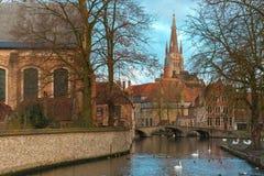 Ajardine no lago Minnewater e na igreja em Bruges Fotos de Stock Royalty Free