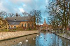 Ajardine no lago Minnewater e na igreja em Bruges Fotos de Stock