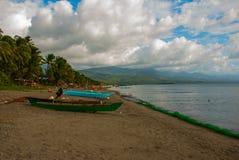 Ajardine o céu com nuvens, montanhas no tempo nebuloso O Sandy Beach vulcânico com barcos Pandan, Panay, Filipinas Imagens de Stock Royalty Free