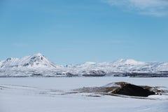 Ajardine o campo de neve com lago congelado e a montanha com o céu azul no inverno Fotos de Stock