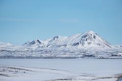 Ajardine o campo de neve com lago congelado e a montanha com o céu azul no inverno Fotografia de Stock