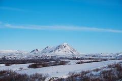 Ajardine o campo de neve com montanha e o céu azul no inverno Imagens de Stock Royalty Free