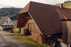 Ajardine o campo do outono com as casas da quinta de madeira no monte verde e nas montanhas no fundo, Alemanha Fotos de Stock Royalty Free