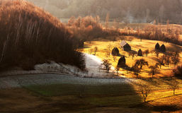 Ajardine o campo do por do sol perto da casa com monte de feno Fotos de Stock