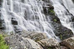 Ajardine o detalhe de cachoeira sobre rochas na exposição longa do verão Imagens de Stock