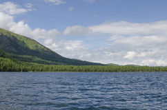 Ajardine o lago azul contra montanhas e madeira Foto de Stock Royalty Free