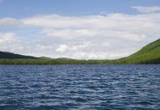 Ajardine o lago azul contra montanhas e madeira Fotografia de Stock Royalty Free