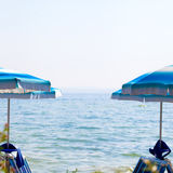 Ajardine o lago Garda com os guarda-chuvas no primeiro plano, Itália Imagem de Stock Royalty Free
