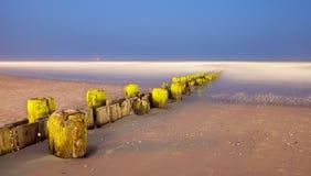 Ajardine o panorama de cargos velhos do cais na praia Fotografia de Stock Royalty Free